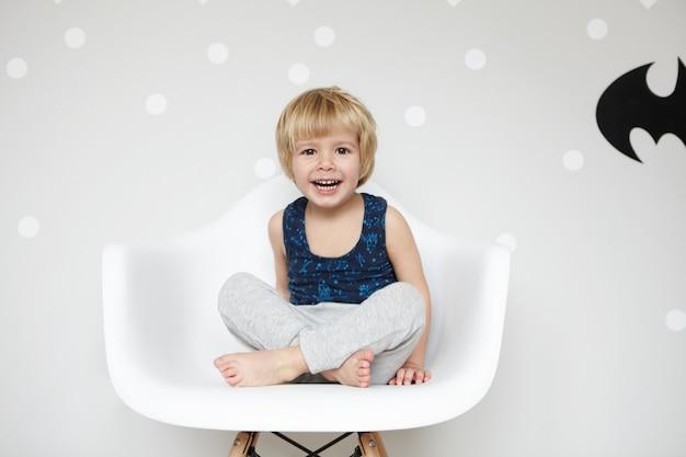 Portret zabawnego malucha z jasnymi włosami w piżamie, siedzącego na krześle ze skrzyżowanymi nogami, śmiejącego się, z szeroko otwartymi ustami, pokazującego białe zęby, wygrywającego na pustej ścianie