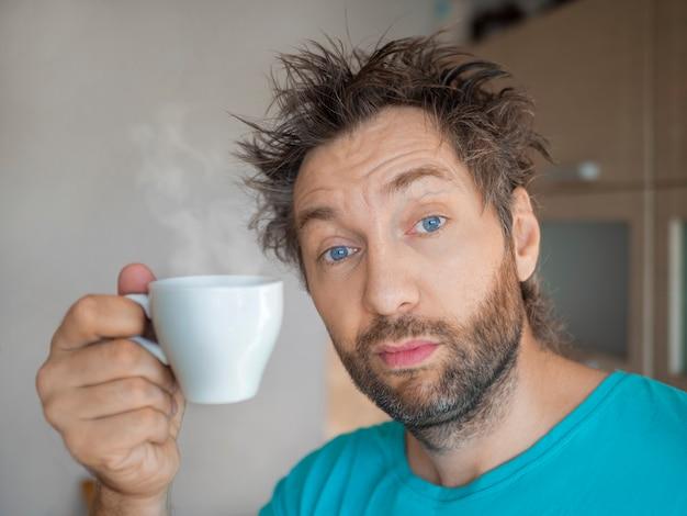 Portret zabawnego mężczyzny po przebudzeniu przy filiżance gorącej kawy lub herbaty