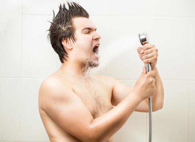 Portret zabawnego mężczyzny śpiewającego pod prysznicem