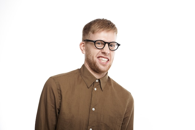 Portret zabawnego młodego nieogolonego mężczyzny w okularach i brązowej koszuli robiący krzywą minę, zaciskając zęby i czując zniesmaczenie z powodu zapachu nieprzyjemnego, złego smrodu, pozowanie na białym tle