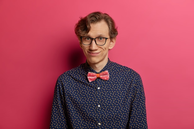 Portret zabawnego pozytywnego modela z zadowolonym wyrazem twarzy, nosi elegancką koszulę, przezroczyste okulary, jest w dobrym nastroju, spotyka się na randce, czeka na dziewczynę, pozuje na różowej ścianie