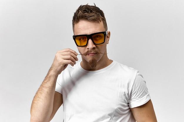 Portret zabawnego, przystojnego młodego europejczyka w białej koszulce i prostokątnych żółtych okularach podczas pracy przed ekranem komputera, kręcąc swoje stylowe wąsy za pomocą wosku do włosów