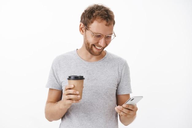 Portret zabawnego szczęśliwego beztroskiego faceta z włosiem, trzymającego papierowy kubek i smartfona, uśmiechającego się szeroko do gadżetu, piszącego na ekranie