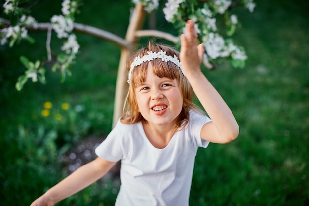 Portret zabawnej dziewczynki 5-6 lat trzymającej kwiat stojący w kwitnącym wiosennym ogrodzie, ubrana w białą sukienkę i kwiatowy wianek na zewnątrz, zbliża się sezon wiosna.