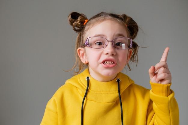 Portret zabawnej słodkiej dziewczynki w czarnych okularach w żółtej bluzie z kapturem ze śmieszną fryzurą