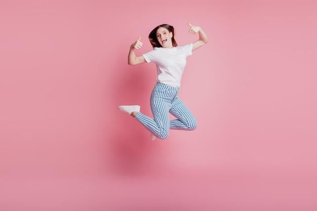Portret zabawnej szalonej dziewczyny skaczącej w powietrzu, unoszącej dwa kciuki w górę na różowym tle