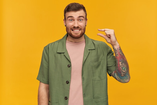 Portret zabawny dorosły mężczyzna z brunetką i włosiem. ubrana w zieloną kurtkę z krótkim rękawem. pokazuje mały rozmiar i chichocze. ma tatuaż. pojedynczo na żółtej ścianie