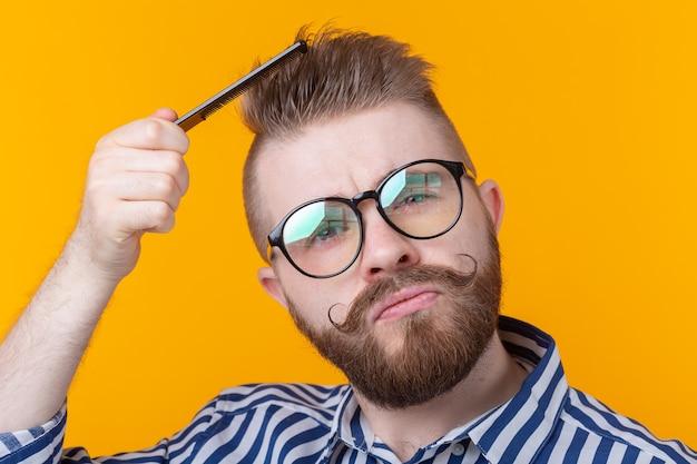 Portret zabawny hipster mężczyzna czesał włosy na żółtej ścianie