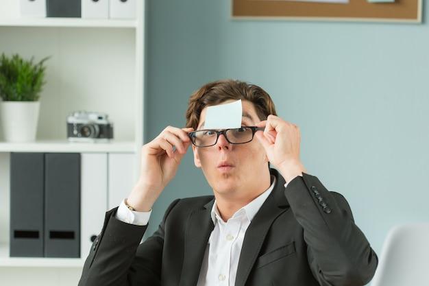 Portret zabawny mężczyzna w okularach i koszuli z niebieskim prześcieradłem przyklejonym do czoła