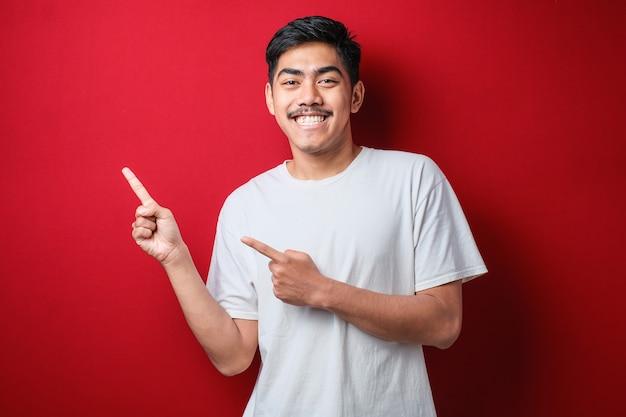Portret zabawny młody azjatycki człowiek w białej koszulce uśmiechający się i wskazujący na prezentację czegoś po jego stronie, na czerwonym tle z kopią przestrzeni