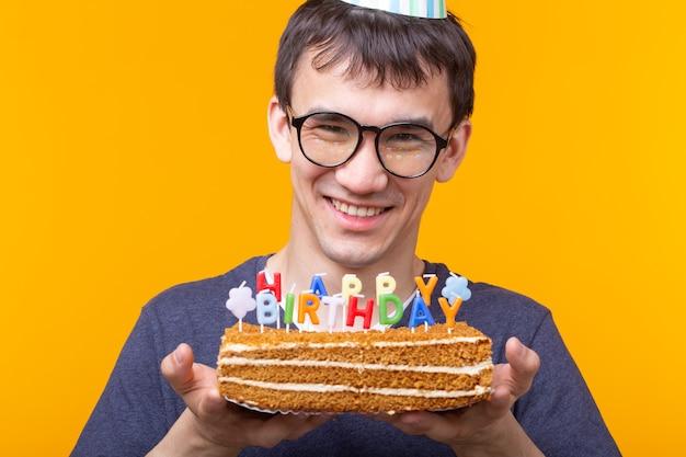 Portret zabawny pozytywny facet w papierowej czapce i okularach, trzymając gratulacyjny domowe ciasto