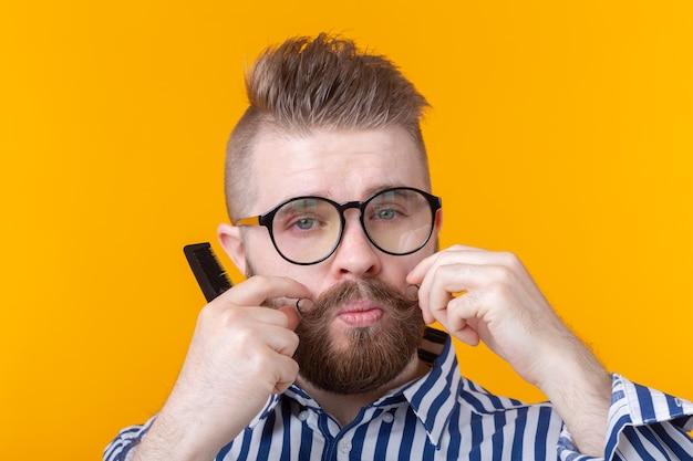 Portret zabawny przystojny młody mężczyzna hipster z wąsami i brodą, czesząc wąsy