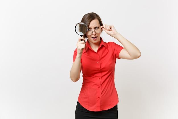 Portret zabawy całkiem młoda kobieta nauczyciel biznesu w czerwonej koszuli okulary gospodarstwa, patrząc przez szkło powiększające na białym tle. edukacja lub nauczanie w koncepcji uniwersytetu w szkole średniej
