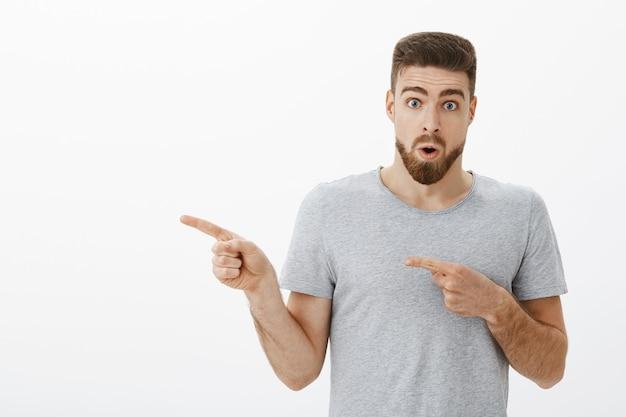 Portret zachwyconego i zdziwionego zainteresowanego przystojnego dojrzałego mężczyzny z brodą dyszącą, składane usta z wow dźwiękiem wskazującym w lewo, pytany o ciekawy nowy pokaz fryzjerski otwarty w pobliżu białej ściany