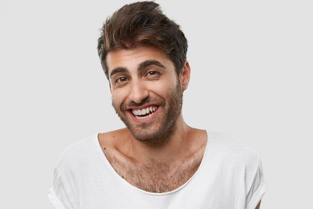 Portret zachwyconego młodego faceta rasy kaukaskiej lubi zabawną historię lub żart, śmieje się radośnie, ma zębaty uśmiech
