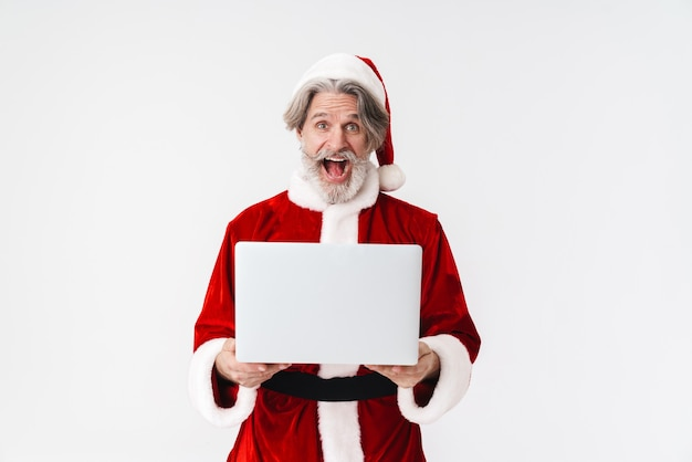 Portret zachwyconego szarego mężczyzny w czerwonym stroju świętego mikołaja, trzymającego laptopa i krzyczącego na białym tle