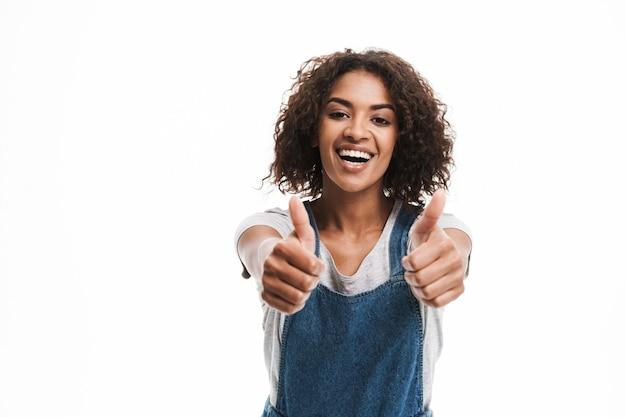 Portret zachwyconej kobiety ubranej w dżinsowe kombinezony, uśmiechającej się z przodu z kciukami do góry odizolowanymi na białej ścianie