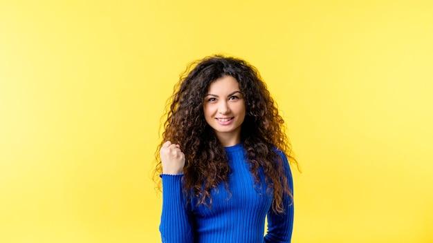 Portret zachwycony brunetka dziewczyna z kręconymi włosami. udane emocjonalne damy co tak, gest zwycięzcy.