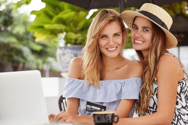 Portret zachwyconych, przyjaznych młodych kobiet o atrakcyjnym wyglądzie, siedzą blisko siebie w kawiarni, otoczone laptopem, używają plastikowej karty do płatności online, cieszą się gorącą aromatyczną kawą