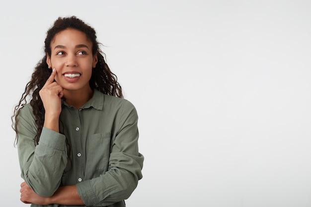 Portret zadowolona atrakcyjna ciemnoskóra kręcona brunetka dama dotyka jej twarzy podniesioną ręką, patrząc na bok z uroczym uśmiechem, stojąc na białym tle