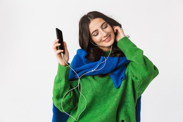 Portret zadowolona kobieta o ciemnych włosach, noszenie słuchawek i trzymając smartfon, podczas gdy na białym tle