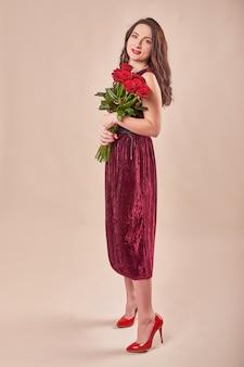 Portret zadowolona młoda kobieta w czerwonej sukience z bukietem róż