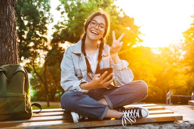 Portret zadowolona śliczna młoda studentka w okularach, siedząca na ławce na zewnątrz w parku przyrody z pięknym światłem słonecznym za pomocą telefonu komórkowego pokazującego znak pokoju