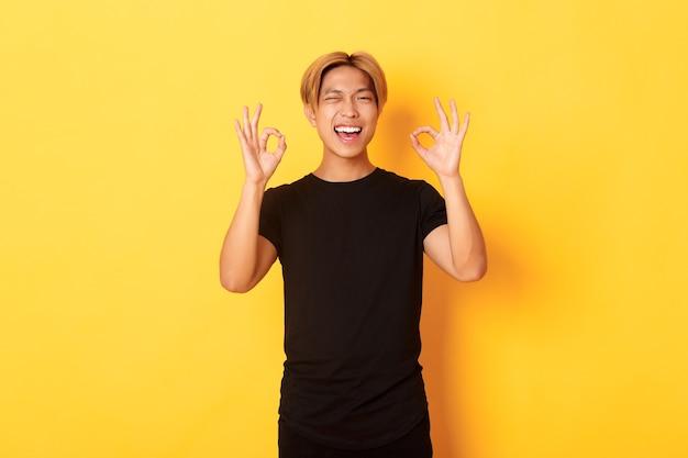 Portret zadowolonego i szczęśliwego azjatyckiego uśmiechniętego faceta, pokazującego dobry gest z aprobatą, mrugający zapewniony, gwarancja jakości, żółta ściana