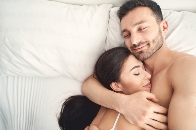 Portret zadowolonego młodego mężczyzny i jego pogodnej żony śpiących w sobie nawzajem