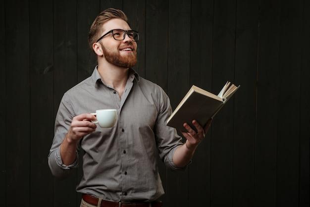 Portret zadowolonego młodego mężczyzny patrzącego w górę, trzymającego otwartą książkę i filiżankę kawy na białym tle na czarnej drewnianej powierzchni