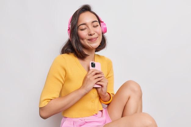 Portret zadowolonej azjatyckiej kobiety o ciemnych włosach lubi ulubioną muzykę doskonały dźwięk w słuchawkach bezprzewodowych trzyma nowoczesną komórkę, która ma zamknięte oczy, nosi ubranie na co dzień na białym tle nad białą ścianą