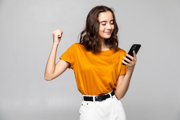 Portret zadowolonej młodej kobiety, trzymając telefon komórkowy i świętuje na białym tle nad szarością