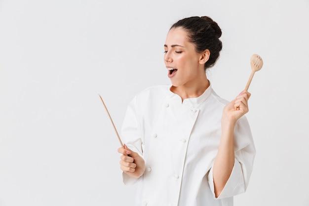 Portret zadowolonej młodej kobiety z naczynia kuchenne
