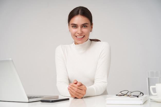 Portret zadowolonej młodej uroczej brunetki kobiety ubranej w białą poloneck składającą ręce na blacie i wyglądającej pozytywnie ze szczerym uśmiechem, odizolowana na białej ścianie