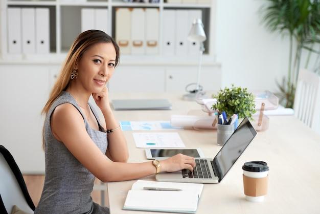 Portret zadowolonej młodej wietnamskiej kobiety biurowej korzystającej z laptopa przy stole z filiżanką kawy i organizerem