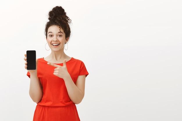 Portret zadowolonej, przystojnej kobiety w czerwonej sukience z kręconymi włosami uczesanymi w kok