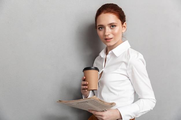Portret zadowolonej rudej bizneswoman 20s ubranej w strój wizytowy, pijącej kawę na wynos i czytającej gazetę w biurze na białym tle nad szarym
