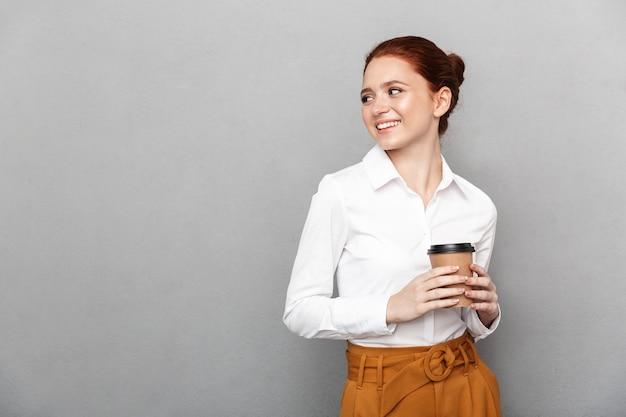 Portret zadowolonej rudej bizneswoman 20s w formalnym stroju uśmiecha się w biurze i pije kawę na wynos z plastikowego kubka izolowanego nad szarym