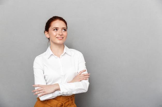 Portret zadowolonej rudowłosej bizneswoman 20s w formalnym stroju, uśmiechniętej i pozującej w biurze na białym tle nad szarym