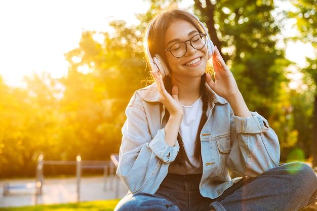Portret zadowolonej szczęśliwej młodej nastoletniej dziewczyny, siedzącej na zewnątrz w pięknym zielonym parku, słuchającej muzyki w słuchawkach