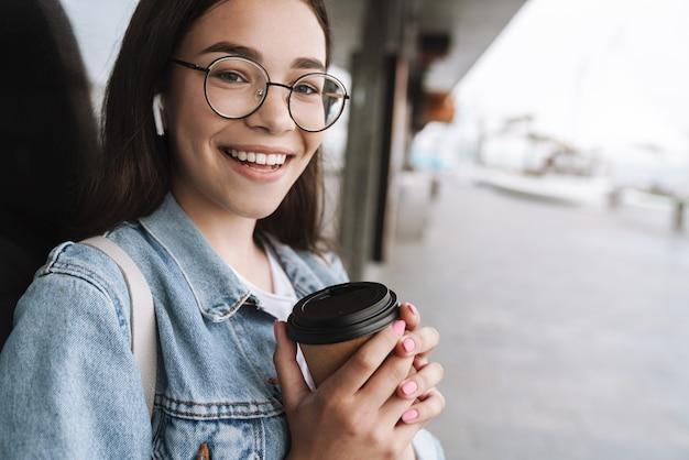 Portret zadowolonej uśmiechniętej nastolatki w okularach i słuchawkach trzymających papierowy kubek kawy na wynos podczas spaceru na świeżym powietrzu