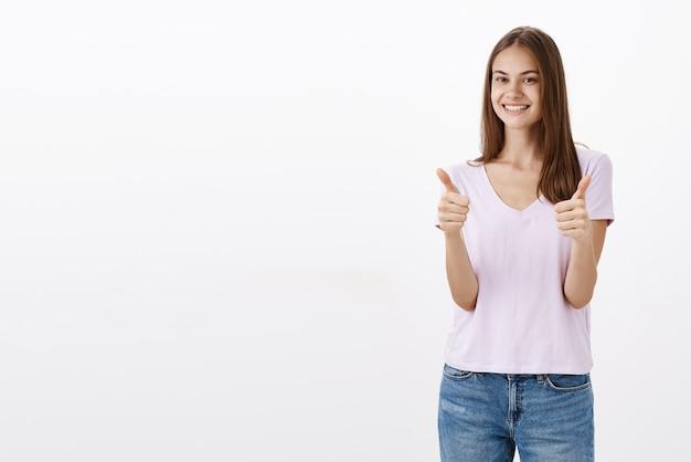 Portret zadowolonej, zadowolonej i zadowolonej przystojnej, sympatycznej kobiety w luźnej bluzce i dżinsach pokazującej kciuki do góry i uśmiechającej się szeroko, zadowolonej z dobrej jakości produktu