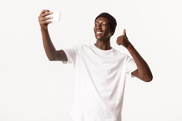 Portret Zadowolony Afroamerykanin W Czapce, Uśmiechnięty Szczęśliwy I Pokazujący Kciuki Do Góry Podczas Robienia Selfie Lub Rozmów Wideo Przez Smartfona Premium Zdjęcia