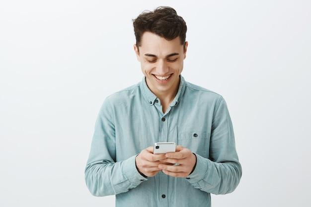 Portret zadowolony beztroski przystojny facet z krótkimi ciemnymi włosami w koszuli