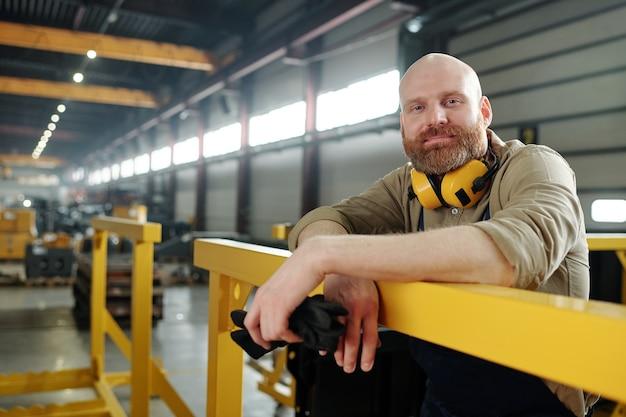 Portret zadowolony, łysy robotnik fizyczny z brodą, trzymając rękawice robocze i opierając się na metalowych balustradach w fabryce