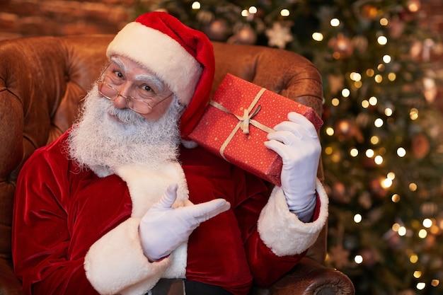Portret zadowolony mikołaj w białych rękawiczkach i czerwonej czapce pozuje z prezentem świątecznym na tle drzewa ...