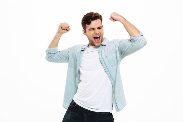 Portret zadowolony młody człowiek świętuje sukces