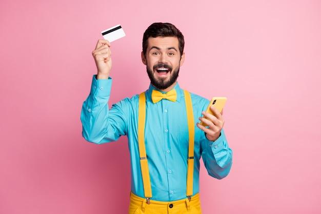 Portret zadowolony podekscytowany facet trzyma komórkę karty bankowej bezpośredni palec puste miejsce