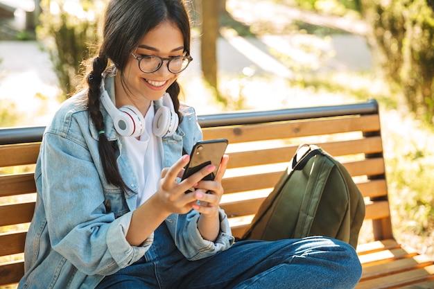 Portret zadowolony pozytywny wesoły ładny młody student dziewczyna w okularach, siedząc na ławce na zewnątrz w parku przyrody przy użyciu telefonu komórkowego.