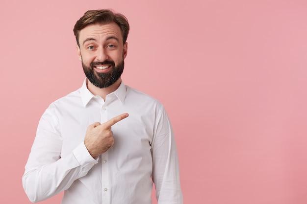 Portret zadowolony przystojny brodaty mężczyzna, ubrany w białą koszulę. szeroko uśmiechnięty, zwraca uwagę na miejsce po prawej stronie, odizolowane na różowym tle.